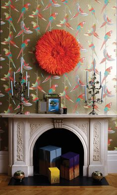 Matthew Williamson in collaboration with Osborne & Little. The Arini Sheer wallpaper from the 2015 Cubana collection. The tropical birds with colourful. metallic plumage are set on contrasting grounds. A bright orange ostrich feather wall decoration compliments the colourful wallpaper as it hovers over a neat fireplace.