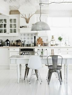 The white is beautiful, but the eclectic chairs, offsetting each other and tying the room together is what makes this space truly special