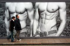 A couple of men walk past a hoarding, in front of the site of a future Abercrombie and Fitch store on Burlington Gardens in London.     Tips and recours|es on friends with benefits. learn more at www.soulmatesandfriends.com