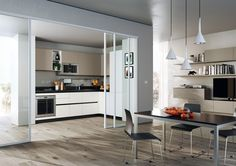Evolution design by Vuesse. Interesting combo: Evolution combines lacquered matt mink to the light of the White decorative columns and base units which is a common colour for suspended wall units and shleves in the living area. Refined detail: black backsplash, top (4 cm thick), grooves and plinths. #Scavolini #Living #kitchens