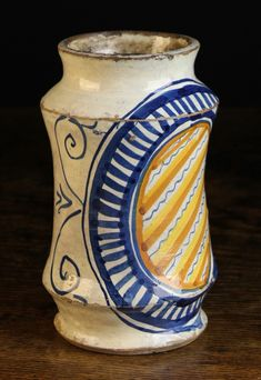 A 15th Italian Century Italian Maiolica Alberello Faenza or Florence.  Circa 1470-1500. The waisted body decorated in blue, yellow and ochre glaze with a large stylised oval armorial crest diagonally striped in a blue ribbed border, 8 ins (20 cms) in height.
