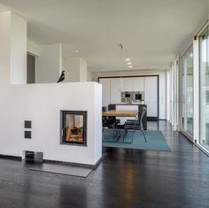 Vintage Inneneinrichtung Haus Pawliczec von Baufritz Modernes Wohnzimmer offen mit Kamin als Raumteiler HausbauDirekt