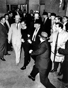 On November 24, 1963, two days after Kennedy's assassination, suspect Lee Harvey Oswald is escorted to the Dallas city jail as Dallas nightclub owner Jack Ruby approaches with gun drawn. Bypassing a cordon of police officers, Ruby shot Oswald in the abdomen, an act inadvertently captured on live television by reporters filming the prisoner transfer. Ruby was convicted of Oswald's murder and spent his remaining days in prison.: