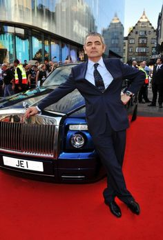 Rowan Atkinson poses by the one-off Rolls-Royce V16 Experimental Phantom Coupé which features in his film Johnny English Reborn.