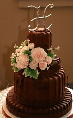 Four tier round chocolate wedding cake with monogram topper and fresh flowers