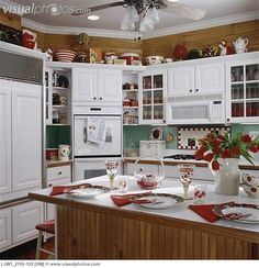 KITCHEN ; cherry theme, with white cabinets & counter tops, natural wood stained wainscot , with view to oven & fridge, cherry motif,  red a...