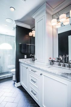 Black and white bathroom features a long washstand, divided into his and hers sections fitted with white cabinets topped with marble framing his and hers sinks under three light linear sconces mounted on vanity mirrors.