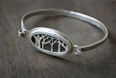 This awesome bracelet lets you wear a window into the woods. Two layers of silver trees are hand cut with a saw and textured through a unique
