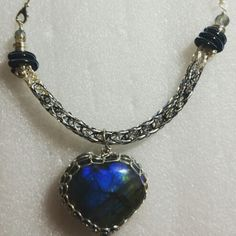 2 tone silver and blue steel Viking Knit necklace with blue steel spiral end caps and a silver Viking Knit wrapped Labradorite heart pendant.