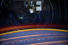 By combining a series of 30-second exposures, astronaut Don Pettit captures circular star trails centered on the station's axis of rotation, along with green airglow on the horizon, smeared-out city lights and lightning storms below.