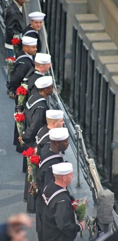 Sailors coming into port to meet their families. (Love they all have flowers behind their back... nice !)
