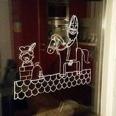 Vrolijke sinterklaas, piet en amerigo op het dak raamtekening om op je raam te tekenen rond 5 december.