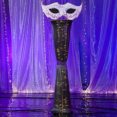 The Masquerade Ball Mask Column features a fabric stretch column with a mask decorated with a purplish pink, white and periwinkle flourish pattern.