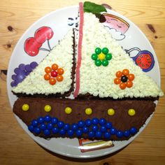 Easy river thames themed sailboat childrens cake! This is a bake-off winner! Made by slicing a basic square cake twice on the diagonal: the middle becomes the base (hull) of the boat and each triangle becomes a sail.  Decorated with piping cream, m&m's and candy.