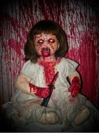 Evil child doll covered in blood and holding a knife