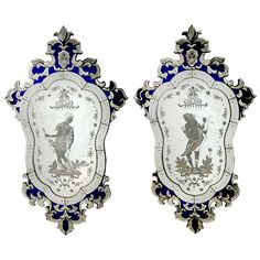 A pair of handcrafted Venetian glass mirrors etched with male and female figures and cobalt blue glass inlay detailing.