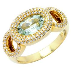 This light catching oval green amethyst glimmers from a frame of brilliant round cut, prong set diamonds. The masterfully handcrafted 14K yellow gold design of the ring features three interlocking, diamond encrusted loops.Different ring sizes may be available. Please inquire for details.