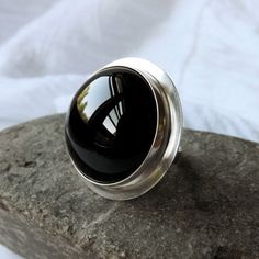 An eye catching statement ring with a large high dome, black onyx cabochon in a…