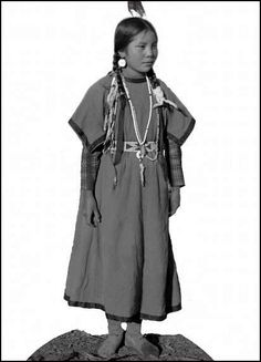 Mat-tie Sup-pee (Mali Supi), a young woman on the Flathead Indian Reservation in western Montana, stands in a dirt area on the reservation. Photo c. 1905.
