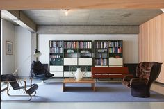 Bare concrete ceiling, shiny resin floor, plastered and wooden walls set the space for a nice list of eccentric furniture. Sofa by Martin Visser for Spectrum, chair  Elda by Joe Colombo (right) and Paimio Chair by Alvar Aalto for Artek (left). Library by André Cordemeyer for Gispen with lamp Magneto by H. Fillekes for Artifort. On the table vase Big Frozen by designer Wieki Somers.