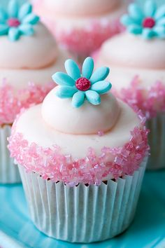 Frosted cupcakes with pink sugar and blue sugar flowers