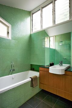 Green penny round bathroom tiles makes this renovation stand out. Styling by Claire Delmar. Photography by Michael Wee.