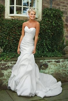 KATHY IRELAND FOR MON CHERI   Style No: E231130    Strapless crinkled taffeta modified mermaid gown with sweetheart neckline, side draped bodice, dropped waist accented with hand-crafted flower and feathers, full bubble pick-up skirt with chapel length train. Removable straps included. Available in silk shantung.