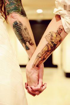 Pareja tomados de las manos mostrando sus tatuajes de star wars