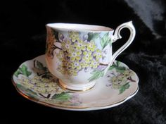 Here is a vintage Royal Albert English bone china tea cup and saucer ..It is called Hawthorn and decorated with branches of pale yellow and white flowers as part of Royal Alberts Flower of the Month series and was made in the 1940s. Marked on the bottom; Royal Albert Bone China England Flower of the Month Series Set of Twelve Hawthorn No 5 Hand Painted.  It is a lovely and delicate design that covers a great deal of the cup and saucer. It is all handpainted and quite beautiful.  It is in…