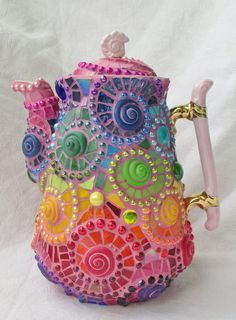 This mosaic teapot is covered with a total of 23 spirals in all colors of the rainbow. The base is a beautiful vintage teapot with a pink spiral knob on the lid. I used all kinds of glass, porcelain, beads, nuggets, tiles and fimo, and then with some trepidation I grouted it in pink - which I probably wouldn't have had the courage to do if I hadn't known all along that this mosaic teapot was going to be for me, to drink tea out of every morning!