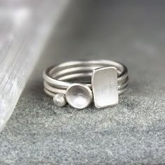 Three minimalist silver stacking rings that are perfect to wear every day or with other stackable rings. Each ring is set with a different shape:
