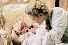 "Marie Antoinette (Kirsten Dunst) with her daughter Marie-Thérèse-Charlotte as depicted in the 2006 film ""Marie Antoinette"". Costume design by Milena Canonero."