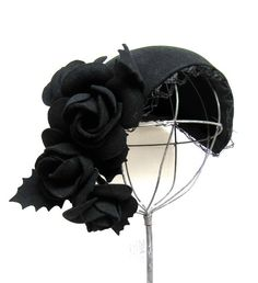 1930s-1940s skullcap with netting along the edges, roses, and holly leaves. Original long hat pin to hold hat securely in place. The flowers drape gracefully to one side.