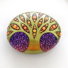 Tree of Life art stone, the stone is a lovely oval shape that fits perfectly in the palm of your hand. The sparkling metallic, green gold tree, branches out across the twilight sky. The dusk sky fading from purple to pink. The leaves/dots have been painted in various shades of red, orange and yellow. Colors of a blooming royal Poinciana tree, like fire in the sky. The glossy branches and trunk of the tree has been accentuated with several coats of a glossy varnish. The dotted sunset…