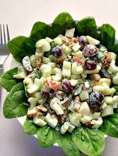 A bowl of Waldorf salad with grapes, celery, walnuts, spinach leaves, apples and a light yogurt dressing.
