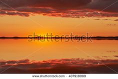Stock Photo: Orange and red sky after the sunset at a lake in Finland. Symmetrical reflection of clouds in the still water.