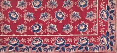 Description Sample of dyed and printed cotton cloth with a white and blue rose and foliate pattern on a red ground. From an unbound pattern book of Turkey red bandanna or shawl designs. Part of the Turkey Red Collection, A.1962.1266.1 - A.1962.1266.78, with subdivisions, totalling c. 40,000 items: Scottish, Dunbartonshire, pre 1855