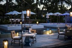Twilight is the perfect time to experience The Deck, where lanterns light the path to comfortable floating lounges and the sun sets between the palm trees.