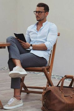 Hot male model wearing chinos and shirt with glasses and brown leather bag