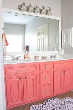 Would be great for a girls bathroom. Coral Vanity. This is really pretty. The gray walls, framed mirror, coral cabinets. Sherwin Williams - coral reef
