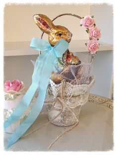 A sweet peat pot has been altered with paint, lace and white tulle. The handle has three sweet roses. Inside sits a vintage style foil rabbit figurine
