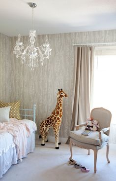 Stunning nursery features faux bois wallpaper, Cole & Son Wood Grain Wallpaper, on walls framing window dressed in taupe curtains across from a turquoise metal daybed dressed in white ruffled bedding, soft pink blanket and gold polka dot pillow alongside a taupe bergere chair and Melissa & Doug Plush Giraffe.