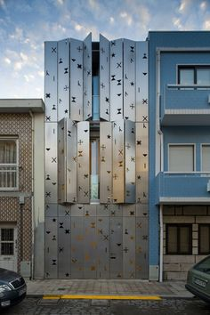 House 77 is a private home located in Portugal and designed by dIONISO LAB. It's tall and narrow, squeezed in between two existing buildings and it has a facade covered by aluminum venetian blinds. 2