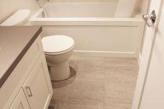 "Beautiful Bathroom Renovation Project Featuring 12"" x 24"" Porcelain Wall Tiles, 12"" x 24"" Porcelain Floor Tiles, Grohe Shower Fixtures, American Standard Toilet, Kohler Undermount Sink, Engineered Quartz Vanity Top, Custom Built Shaker Style Suspended Vanity, and Kohler Bathroom Medicine Cabinet."