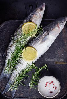 Fresh Mullet - Fresh Mullet on a marble board over stone vintage black background with rosemary and lemon seasoned with salt and rose pepper. Top View