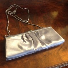 """Silver Satin Handbag or Clutch Purse ~ NITEBAGS ~ Lovely silver chrome frame & gathered satin clutch becomes a shoulder bag when the chain is released from inside. Stylish kiss-closure. Inside fully lined in a silver fabric with one small side pocket. Measures 11"""" wide towards bottom, 9 1/2"""" wide towards top x 4"""" long (w/chain 26"""").  In great condition with a light small mark on one side (see close-up pic) that can be covered up if prefer with a vintage brooch. From a smoke-free home…"""
