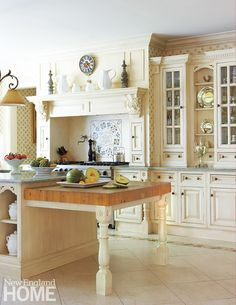 The Clive Christian kitchen plays with rich detailing in the cabinetry and turned legs of the island and range area. Rinfret accented the space with an iron chandelier and wallpaper.