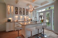 French doors, hardwood floors, white cabinets, painted white brick wall/backsplash. lovely