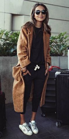 Julie Sarinana + pair of cropped black tracksuit pants + matching black tee + white sneakers + long brown maxi coat + comfort factor + travel look Coat: Ganni.