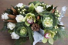 Magnolia leaves (brown), white roses, white Hypericum berries, green Cymbidium orchids (green flower with red tips), decorative cabbage, pine cone, cedar (feather-like greenery), Dusty Miller (gray leaves)